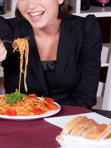 woman eating pasta in a restaurant