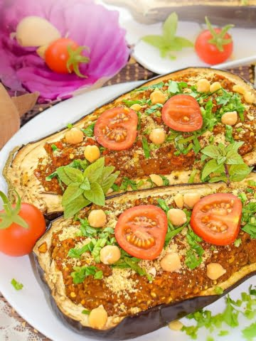 Hearty and tasty Chickpea and Tomato Stuffed Eggplant recipe! Full of flavor and fresh seasonal vegetables, you are going to love this recipe. It is 100% vegan, prepared with only whole plant-food ingredients. Super delicious filling with a chewy texture from the mashed chickpeas!