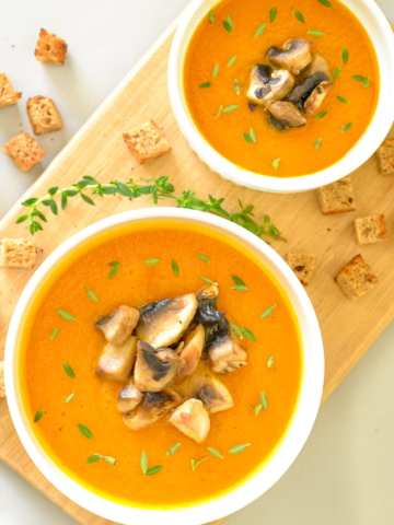two bowls of vegan carrot and curry cream soup overhead shot