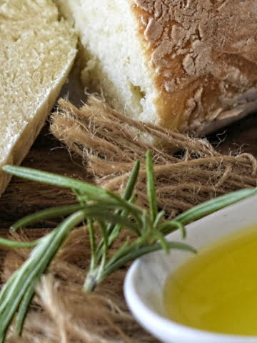 ¾ view of a spoon of olive oil and sliced white bread