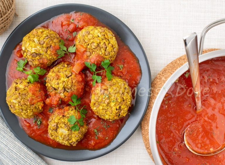 the vegan meatballs in a plate and a pot of tomato sauce