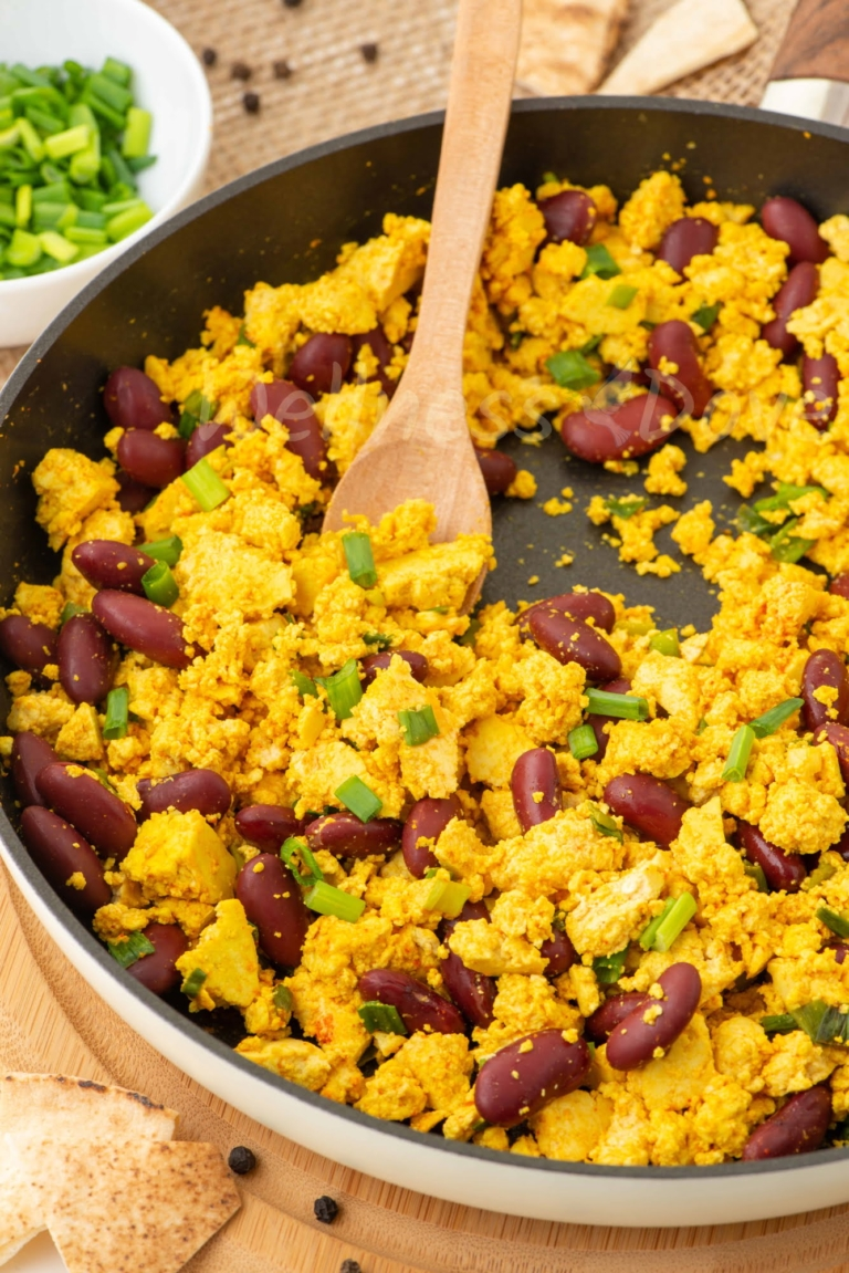 the tofu scramble, 3/4 angle, a wooden spoon taking some of it out