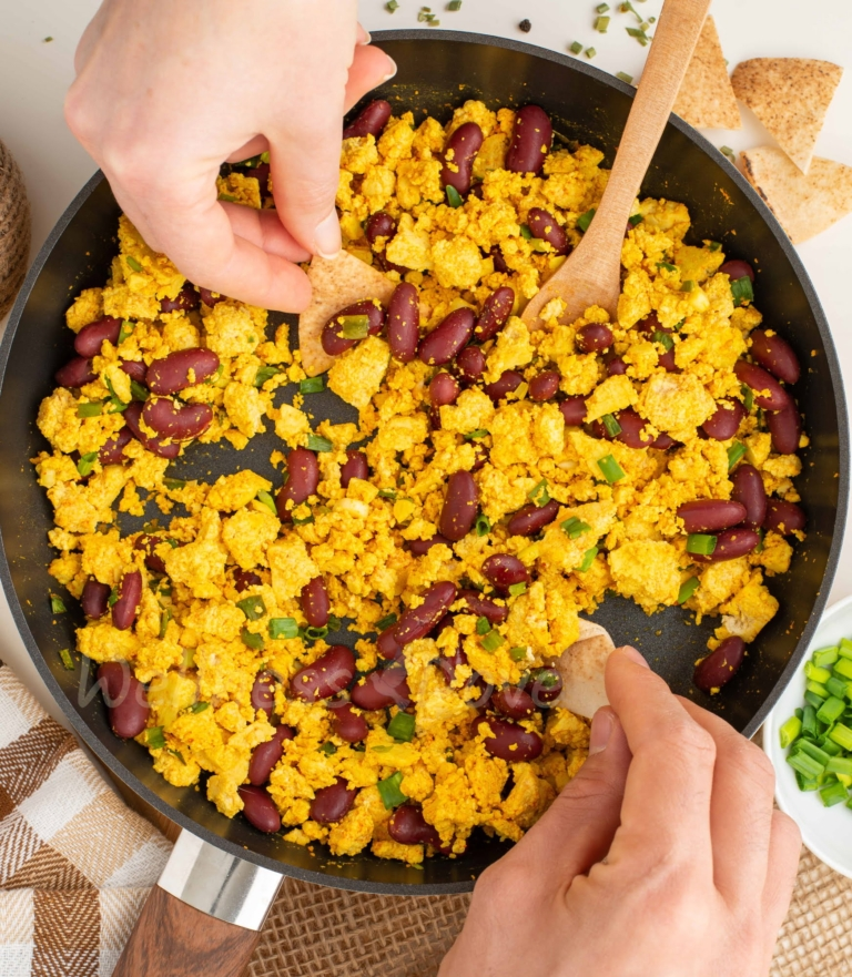 overhead view, two hands dipping bread in the scramble
