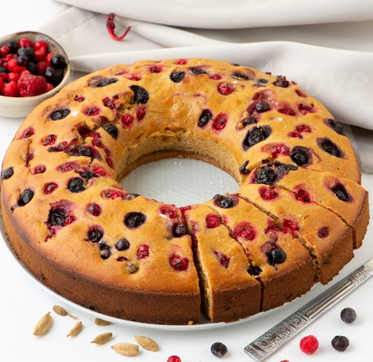 vegan berry bundt cake from 3.4 view, whole with some pieces cut