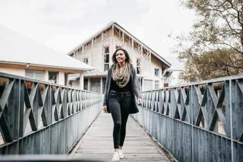 Smiling woman walking on a bridge