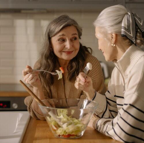 two mature women eating salad